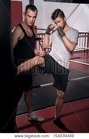 Pinpoint shot. Handsome bearded man is training kick boxing hook on punch bag with help of personal trainer.