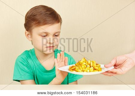 Little cute unhappy boy refuses to eat a fried potatoes