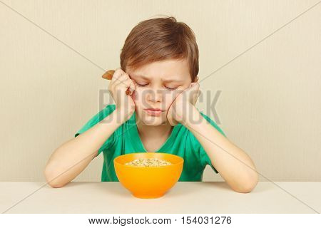 Little discontented boy does not want to eat a porridge