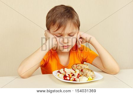Little displeased boy does not want to eat a pasta with rissole