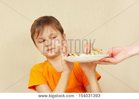 Little displeased boy refuses to eat a pasta with cutlet