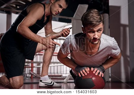 Always ready. Youthful bearded man push-ups by holding his arms on special fitness ball while his trainer counting.