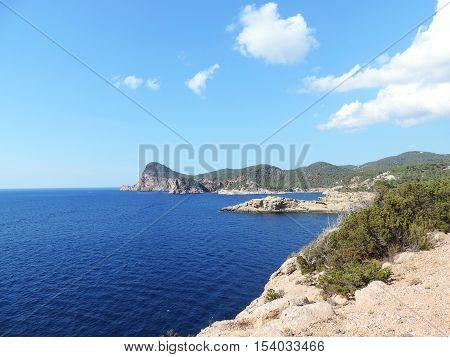Coastline, cliff coast on Ibiza Island with blue sky and fluffy cloudscape.