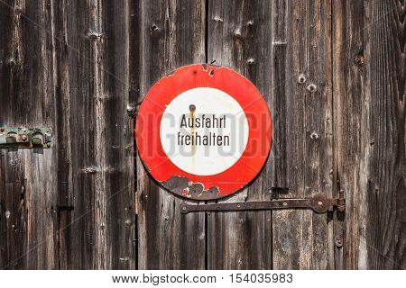 Prohibitory sign in german. Ausfahrt freihalten (keep exit clear). Old sign on a wooden door