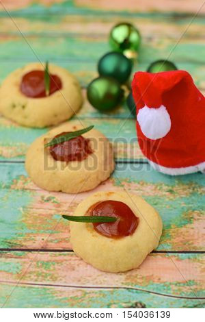 Homemade thumbprint berry rosemary Christmas cookies with green wood background