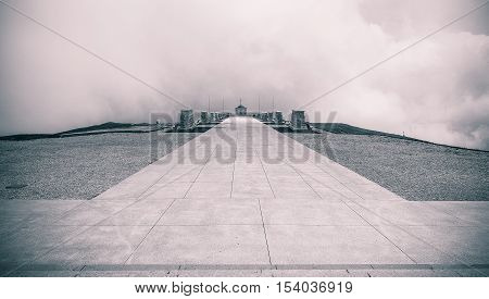 Emotional landscape view of Monte Grappa Sanctuary memorial and cemetery for WWI italian and austrian soldiers b&w intentionally grained