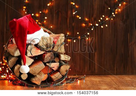 Stack of firewood, garland and Santa Claus hat on wooden background