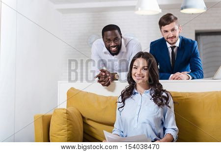 Ready to work productively. Cheeful delighted smiling woman sitting on the couch and smiling while her colleagues standing in the background