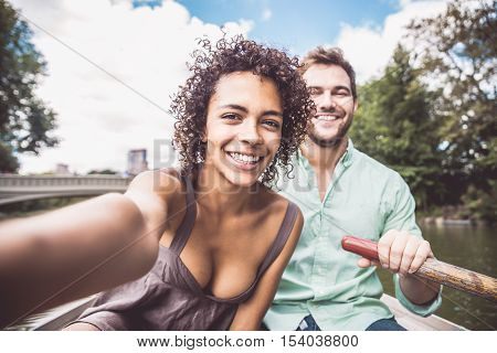 Happy couple having fun on a boat in Central Park - Interracial couple taking a selfie while sightseeing Manhattan