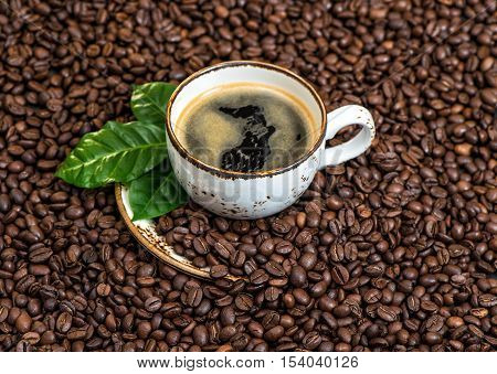 Black coffee with green leaves on caffee beans background. Food und drinks