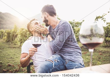 Gay couple at a romantic date having fun and drinking wine - Homosexual pair kissing