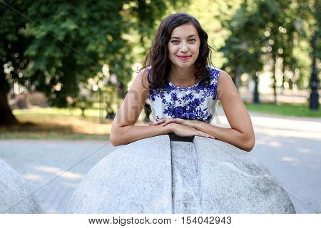 Woman and one huge concrete ball. Outdoor