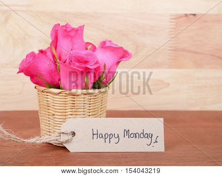 Pink rose flower in the basket and handwriting Happy Monday brown label with wood background