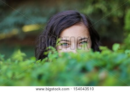 Cunning glance from a woman behind the bushes.