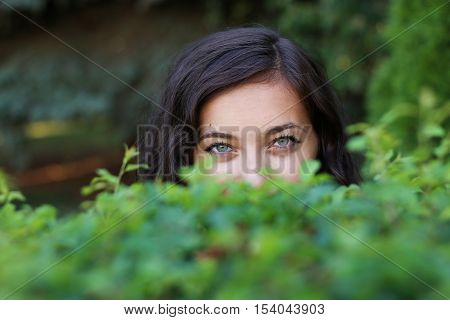 Glance from a woman behind the bushes.