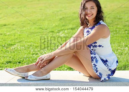 Young sexy woman sitting on the kerb in a short dress.