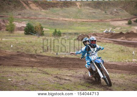 24 september 2016 - Volgsk, Russia, MX moto cross racing - two girls bike riders make selfy riding motorcycle, telephoto