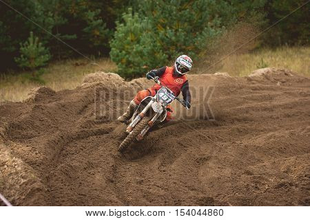 24 september 2016 - Volgsk, Russia, MX moto cross racing - the motorcycle rider in red suit comes to a turn and throwing a spray of dirt, telephoto