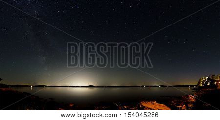 Panorama of the night sky above lake Mjörn in Sweden. The Milky Way is visible on the left side and the bright light of large cities on the opposite side of the lake. In the foreground is the rocky coastline.
