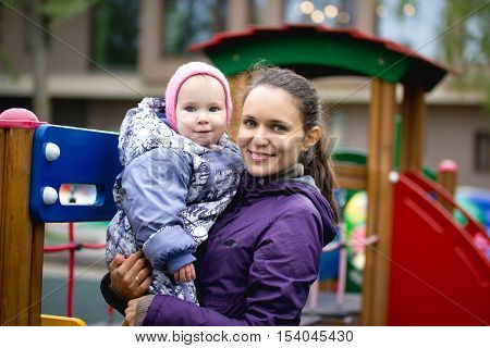 Happy family: Mother and child - little girl walking in autumn park: baby and mammy posing at playground, close up, telephoto shot