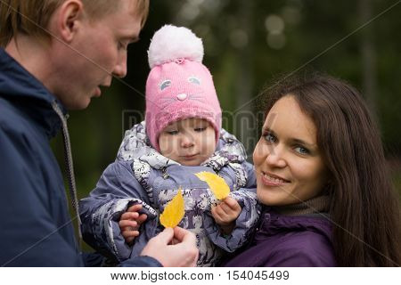 Happy family: Father, Mother and child - in autumn park: dad, mammy baby posing outdoor, girl holding in the hands of the fallen leaves, close up, telephoto shot