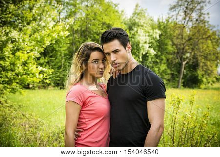 Boyfriend and girlfriend standing in countryside in green luscious field, embracing each other and cuddling, showing romantic love