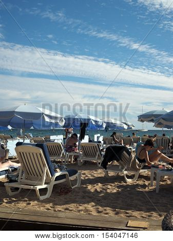 CANNES-SEPT. 13: Sunbathers are seen enjoying the famous beach in Cannes France just off Promenade de la Croisette on September 13 2015.