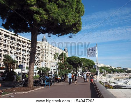 CANNES-SEPT. 13: Tourists walk along famous Promenade de la Croisette in front of historic Carlton Hotel in Cannes France The French Riviera on September 13 2016.