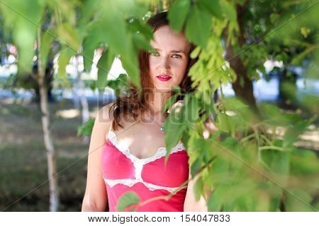 Portrait of a young Frenchwoman in the branches of trees.