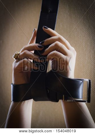Girl has hands bound with leather belt - illustrate pretty nail manicure, extremely close up