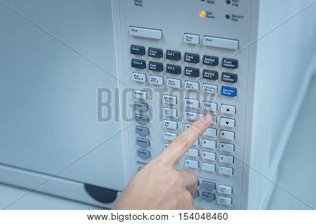 Scientist sets chromatograph oven temperature.  Chemistry lab