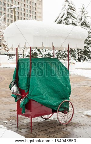 closed seller cart under snow at the street in offseason