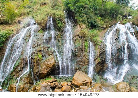 Waterfall Flowing Out From The Trees Against The Rocks