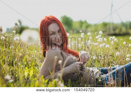Young fashionable attractive sexy girl in glasses sitting on a marguerite-meadow at sunny summer day, horizontal