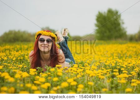 Young fashionable attractive sexy girl with a wreath on her head and glasses lying on a marguerite-meadow at sunny summer day, horizontal