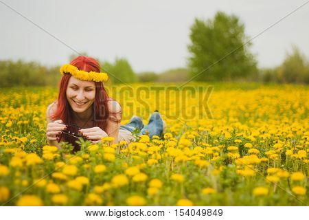Young fashionable attractive sexy girl with a wreath on her head and glasses lying on a marguerite-meadow and smiling at sunny summer day, horizontal