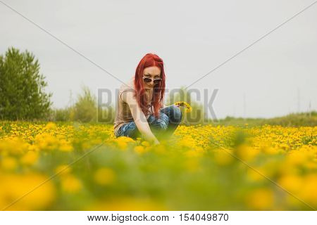 Young fashionable attractive sexy girl with a wreath on her head and glasses sitting on a marguerite-meadow and smiling at sunny summer day, horizontal