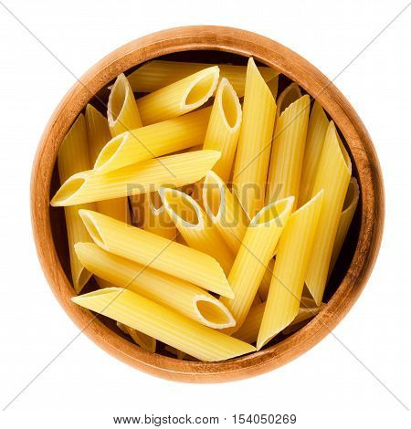 Penne rigate pasta in wooden bowl. Uncooked dried durum wheat semolina noodles. Short-cut medium length tubes with ridges cut diagonally at both ends. Isolated macro food photo over white background.