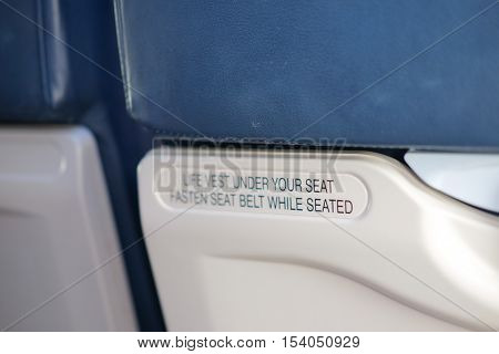 airplane seat with life vest under your seat and fasten seat belt text