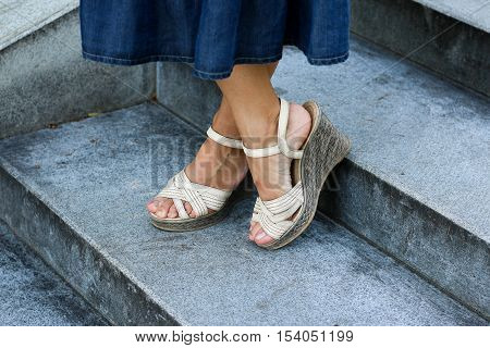 Women's feet in the shoes of high soles.