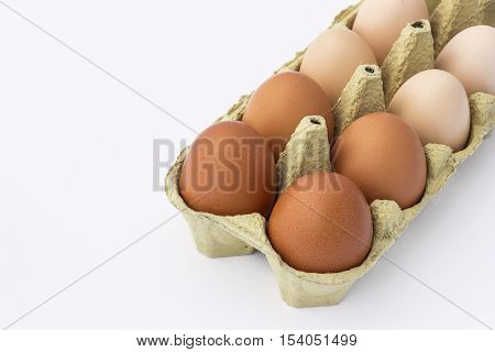 Hen eggs in a paper container isolated on a white background