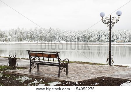 wrought urn bench and lantern on a background of a winter park and lake