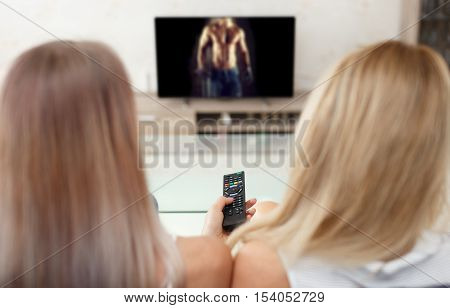 Women watching sexy man video in TV at living room