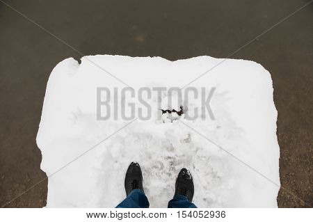 feet in mens black boots and jeans are in snow on bridge before water