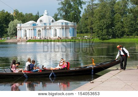 TSARSKOYE SELO, SAINT - PETERSBURG, RUSSIA - JULY 25, 2016: Gondolier and people in the gondola on The Great Pond in The Catherine Park. On the background is The Grotto Pavilion.