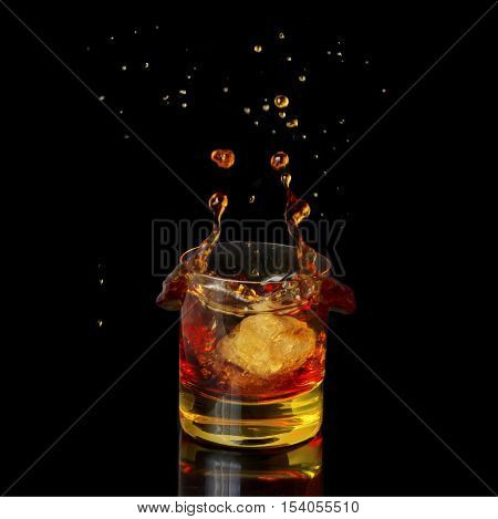 Isolated shot of whiskey with falling ice on black background
