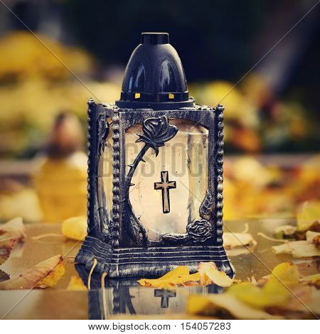 Beautiful Autumn Concept To The Cemetery And Halloween. Candle In A Lantern On The Grave. Background