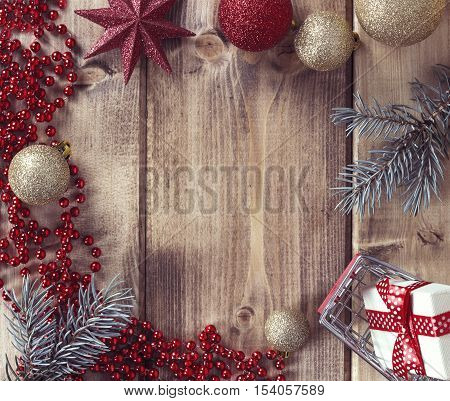 Christmas frame with Christmas balls gift and shopping basket on a wooden background