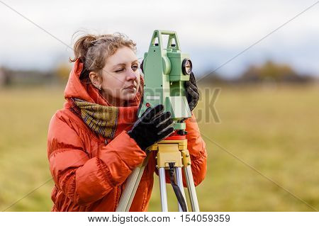 Girl Surveyor works with total station on the field.