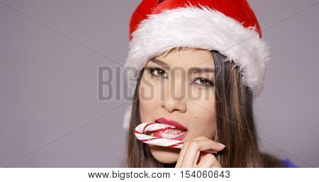 Sensuous young woman sucking on a candy cane